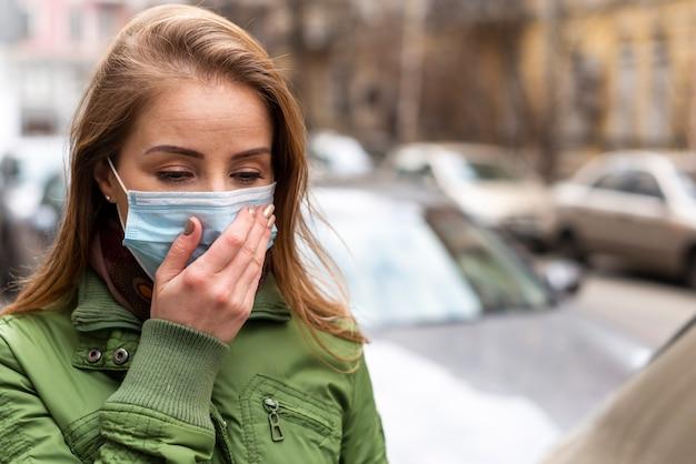 Femme portant un masque et tenant sa main sur son visage