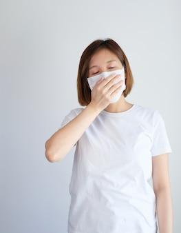 Une femme portant un masque tombe malade à cause du virus corona, covid19, symptôme de grippe comme éternuements, toux, fièvre, courbatures, respiration, douleur.