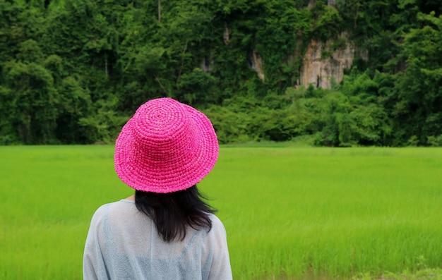Femme portant de la paille rose vif