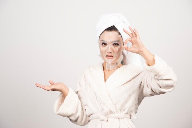 Femme portant un peignoir et une serviette avec masque facial.