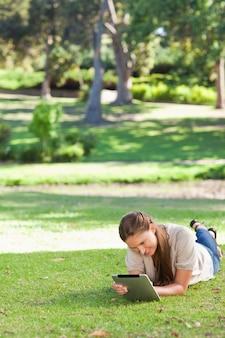 Femme portant sur la pelouse à l'aide d'une tablette