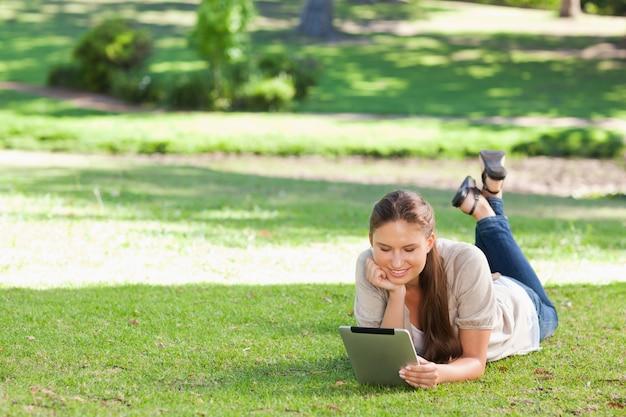 Femme portant sur la pelouse avec une tablette