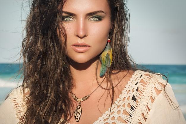 Femme portant un pendentif en bois et des boucles d'oreilles en plumes