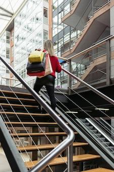 Femme portant un pull rouge en montant les escaliers d'un centre commercial transportant des sacs à provisions.