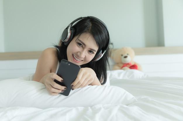 Femme portant des pyjamas verts dorment des écouteurs de musique