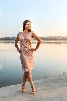 Femme portant une robe de couleur pêche du soir contre le lac