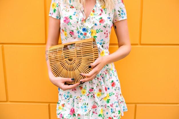 Femme portant une robe à fleurs et tenant un sac de paille, posant près de mur jaune
