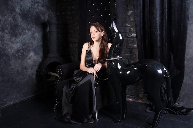 Femme portant une robe noire formelle assise sur le trône à côté d'une statue de chien en laisse