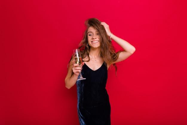 Femme portant une robe noire et tenant un verre de champagne posant sur rouge