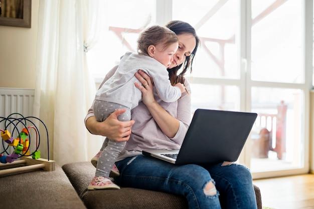 Femme portant sa fille tout en utilisant un ordinateur portable