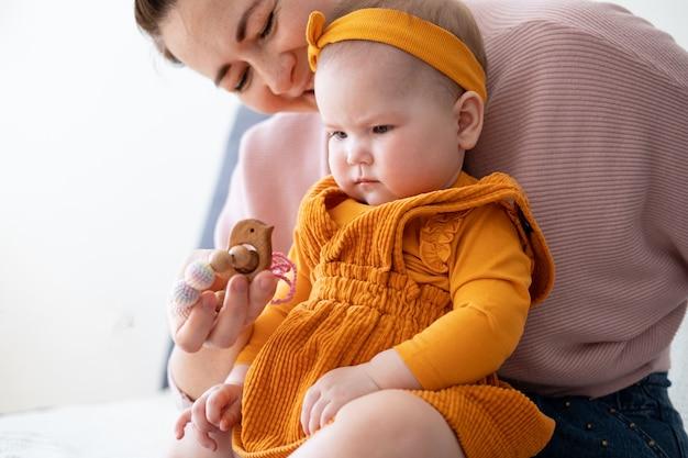 Femme portant sa petite fille. bébé fille joue avec des perles de dentition.