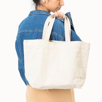Femme portant un sac à provisions réutilisable blanc shoot studio