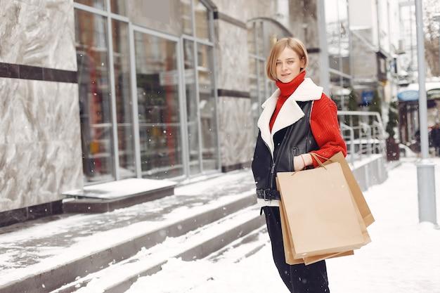 Femme portant des sacs à provisions dans un centre commercial en plein air