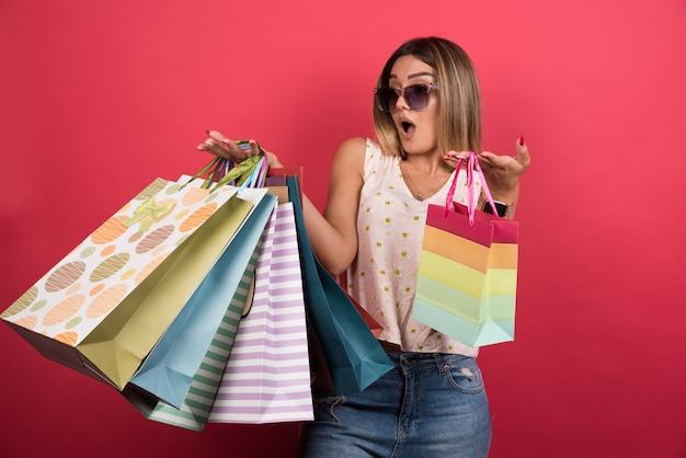 Femme portant des sacs à provisions avec une expression surprise sur le mur rouge.