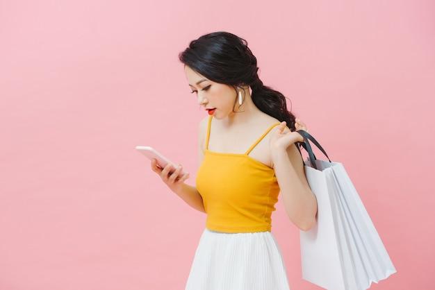 Femme portant des sacs à provisions et des sms au téléphone