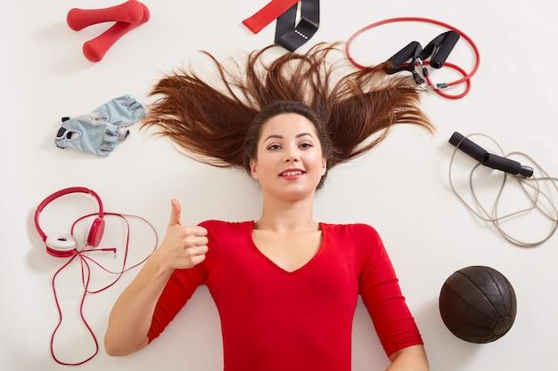 Femme portant sur un sol blanc après avoir travaillé avec des haltères et d'autres équipements sportifs, semble heureuse, montrant le pouce vers le haut, une fille aux cheveux noirs portant des vêtements rouges. concept de mode de vie sain et de remise en forme.