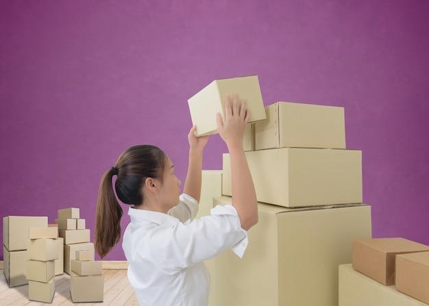 Femme portant et soulevant des boîtes