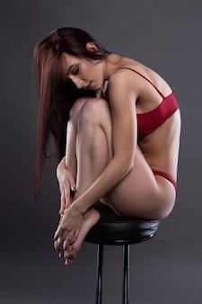 Femme portant des sous-vêtements sexy assis sur une chaise