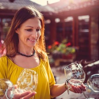 Femme portant des verres à vin sur la cour arrière