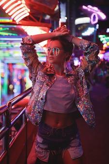 Femme portant une veste étincelante dans la rue avec des néons