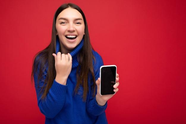 Femme portant des vêtements élégants et décontractés debout isolée sur fond avec espace de copie tenant et utilisant un téléphone portable regardant sur le côté et criant.