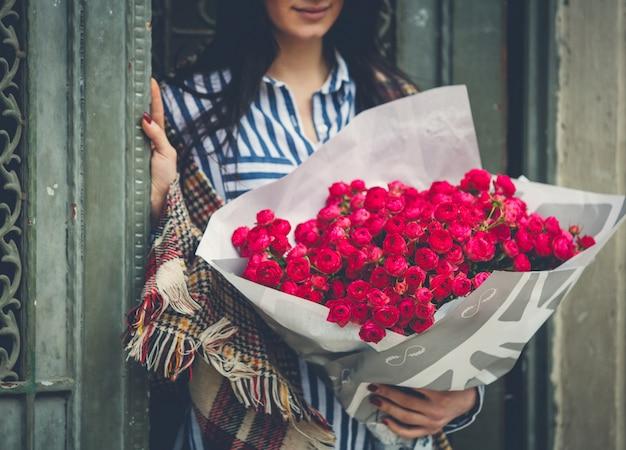 Femme à la porte avec un bouquet de grandes fleurs roses
