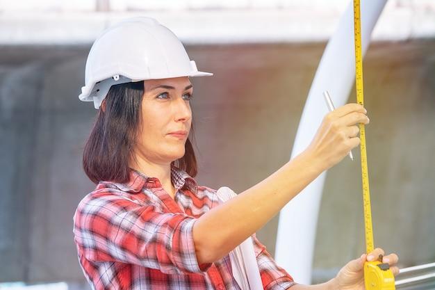 Une femme porte un chapeau de sécurité blanc travaille sur un chantier de construction