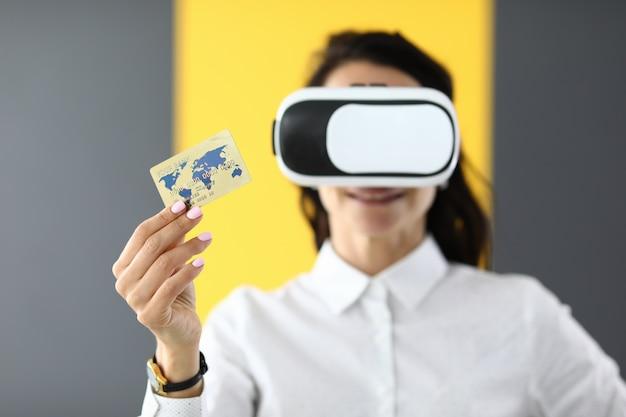 Femme porte des lunettes de réalité virtuelle dans ses mains, elle tient une carte de crédit bancaire