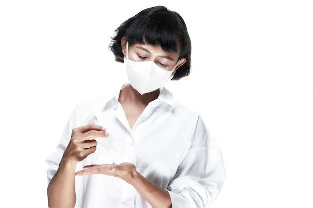La femme porte le masque blanc et verse le gel d'alcool dans la main.
