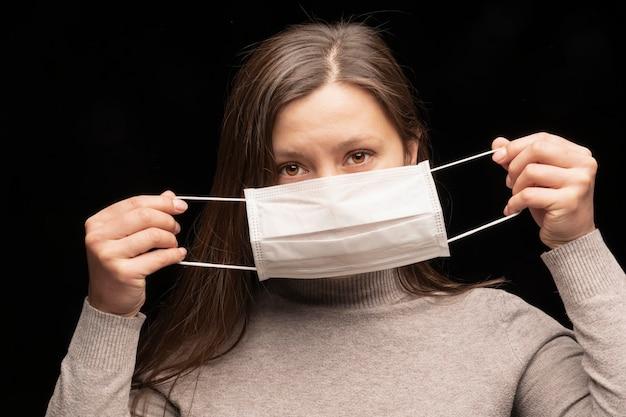 Une femme porte un masque médical blanc du coronavirus. protection contre les infections, la démonstration. la médecine exige le port d'un équipement de protection. portrait de gros plan