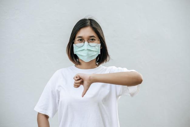 La femme porte un masque et pointe son pouce vers le bas.