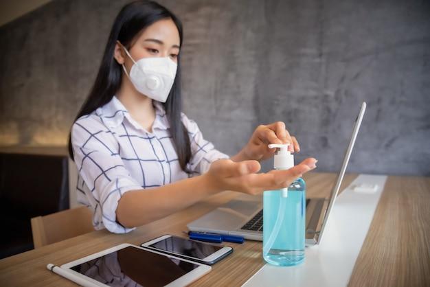 Une femme porte un masque de protection et utilise du gel d'alcool