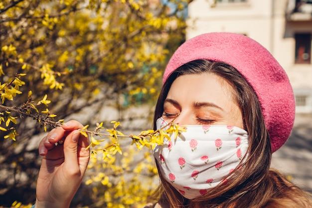 Une femme porte un masque réutilisable à l'extérieur pendant la pandémie de coronavirus covid-19. femme sent les fleurs. restez en sécurité