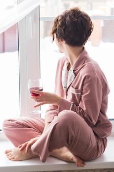 Femme porte un pyjama avec un verre de vin rouge est assis sur le rebord de la fenêtre près de la belle fenêtre à la maison.