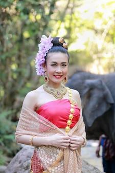 Une femme porte une robe thaïlandaise avec son éléphant