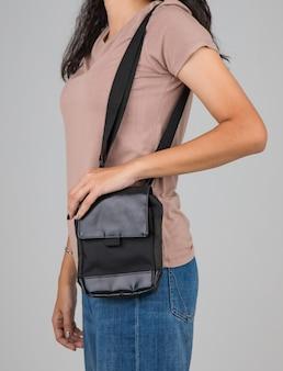 La femme porte le sac décontracté sur l'épaule avec un geste actif et facile.