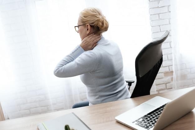 La femme porte ses mains à son cou.