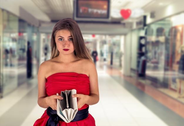 Femme avec portefeuille vide dans le centre commercial