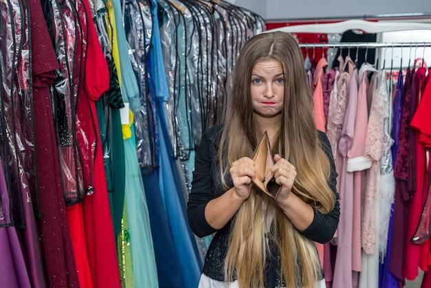 Femme avec portefeuille vide en magasin de vêtements