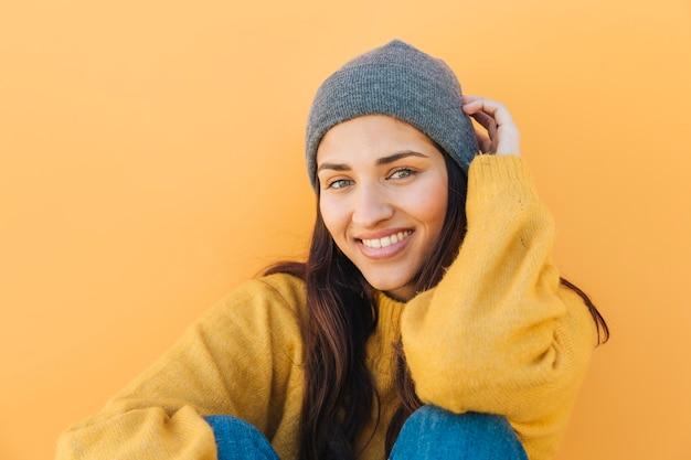 Femme, porter, chapeau tricoté, contre, surface jaune