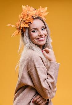 Femme, porter, feuilles érable, diadème, poser, contre, mur jaune