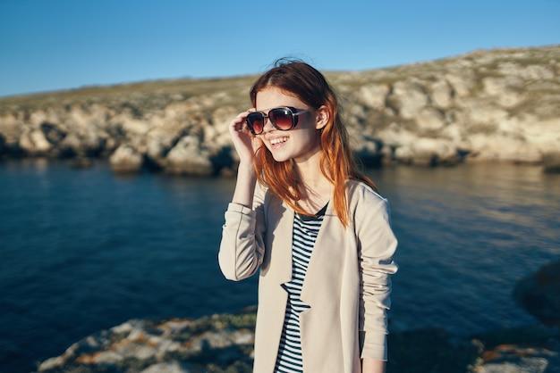 Femme, porter, lunettes soleil, rochers, paysage, mer