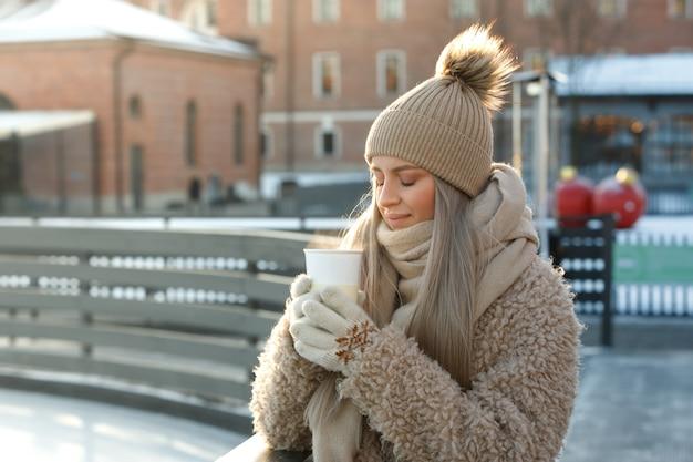 Femme porter des mitaines blanches tenant une tasse blanche fumante de café chaud ou de thé en froide journée ensoleillée d'hiver