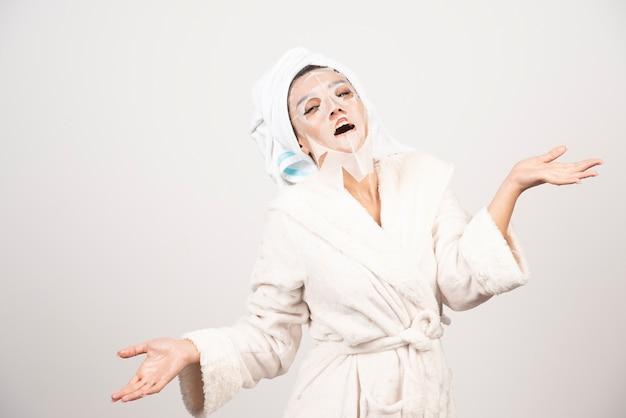 Femme, porter, peignoir, et, serviette, à, masque facial