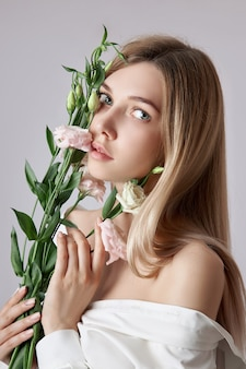 Femme de portrait de beauté avec des fleurs roses d'eustoma dans ses mains. cosmétiques naturels pour les soins de la peau du visage et du corps. belle fille dans une chemise blanche
