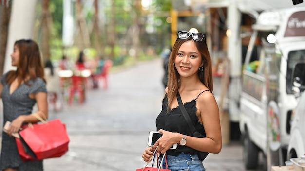 Femme de portrait dans le parc de la rue avec une confiserie en arrière-plan