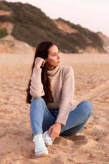 Femme posant au bord de la plage sur le sable