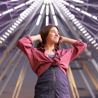 Femme posant au parc d'attractions à côté de la grande roue