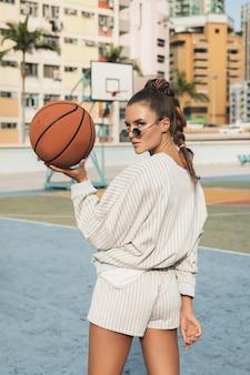 Femme posant avec basket-ball sur terrain de basket