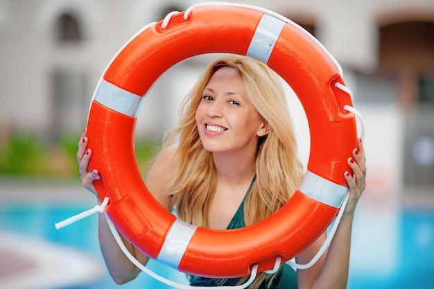 Femme posant avec bouée de sauvetage sur la plage près de la tour de sauveteur bleu journée ensoleillée